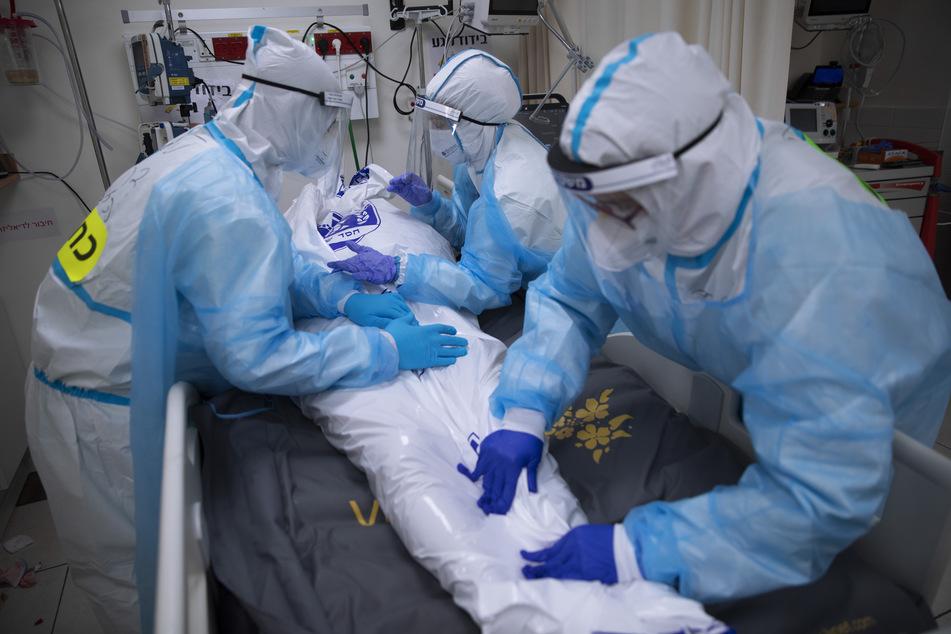 Medizinisches Personal bedeckt den Körper eines Mannes, der an den Folgen von Covid-19 verstorben ist.