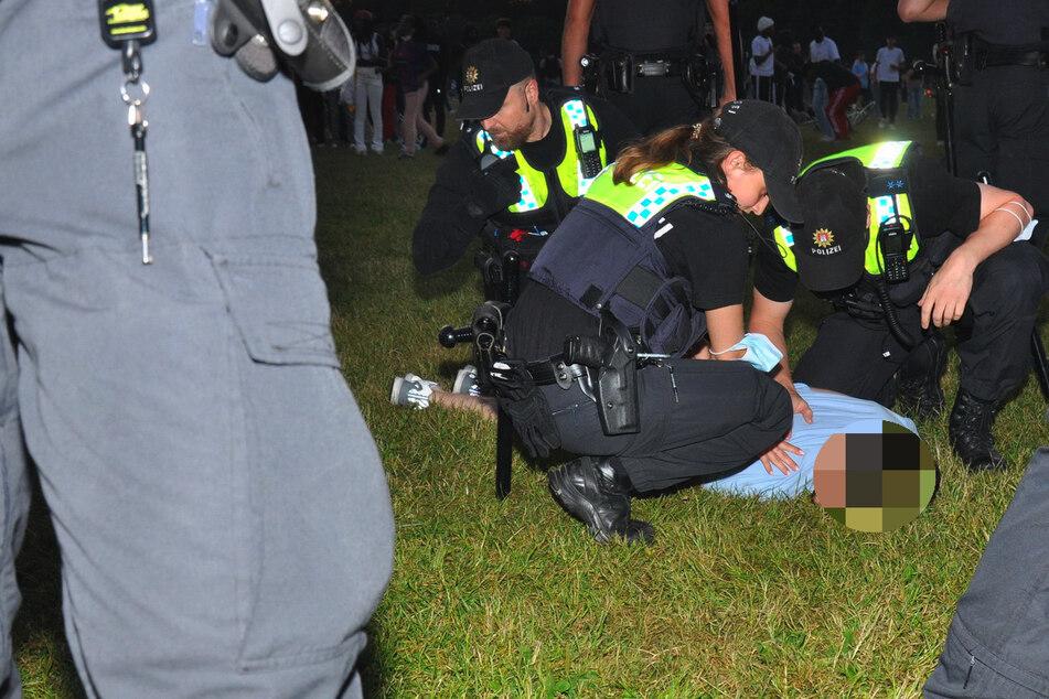Polizeibeamte halten einen Mann im Stadtpark am Boden fest.