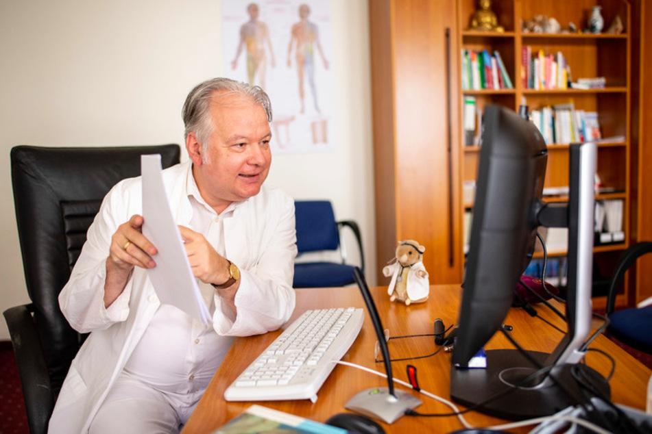 Dr. Wilhelm Schröttle, Hausarzt und Facharzt für Innere Medizin, Manuelle Medizin und Akupunktur, spricht in seiner Praxis über einen Video-Anruf.