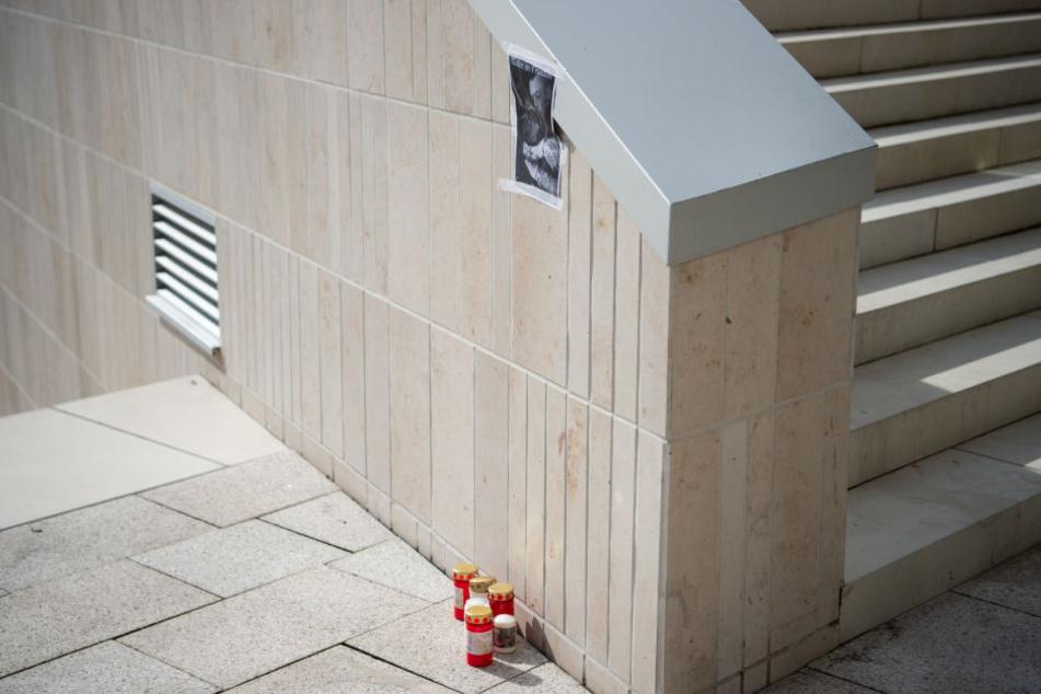 An einer Treppe stehen Kerzen unter einem Foto des Opfers.