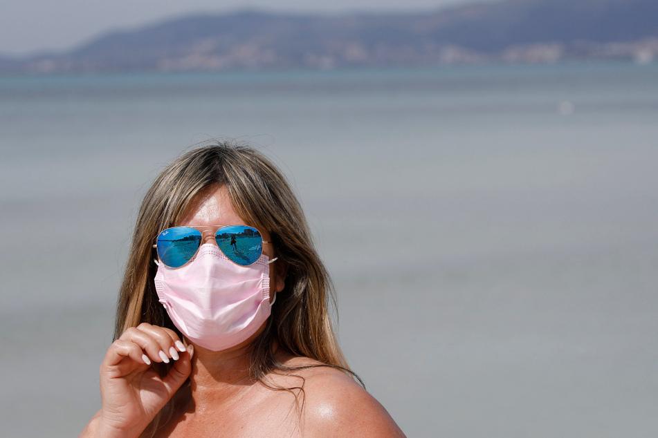 Nadine aus Zürich trägt eine medizinische Maske, während sie die Sonne am Strand von El Arenal genießt.