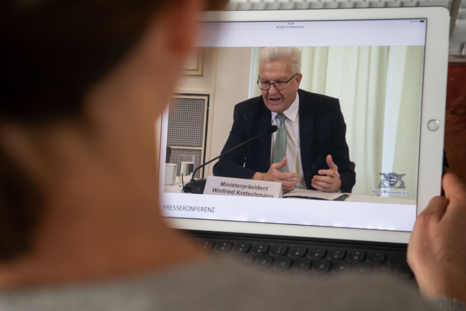 Eine Frau verfolgt auf einem Tablet eine Pressekonferenz, an der Winfried Kretschmann, Ministerpräsident von Baden-Württemberg, teilnimmt. Die Pressekonferenz der Landesregierung fand angesichts der Lage nur per Livestream statt.