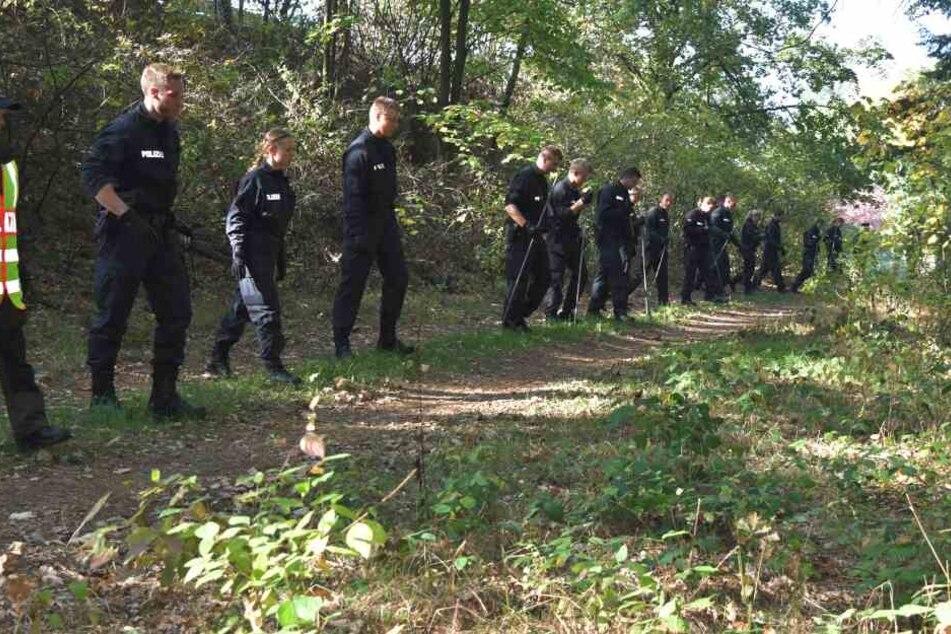 Die Beamten durchforsten das Waldstück, in dem die Knochen gefunden wurden.