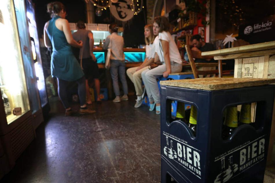 Späte Gäste des Spätis sitzen vor einem Kühlschrank mit Getränken und stehen an der Theke an.