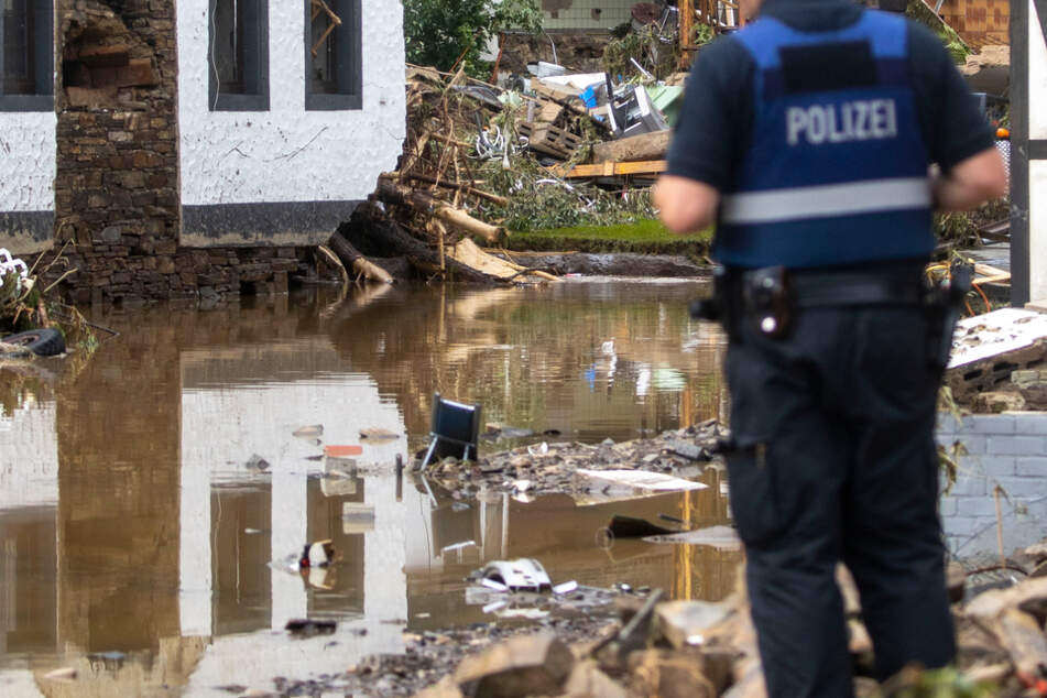 Ein Polizist verschafft sich in dem Dorf Schuld im Kreis Ahrweiler nach den Überschwemmungen einen Überblick. Mindestens sechs Häuser wurden hier durch die Fluten zerstört.