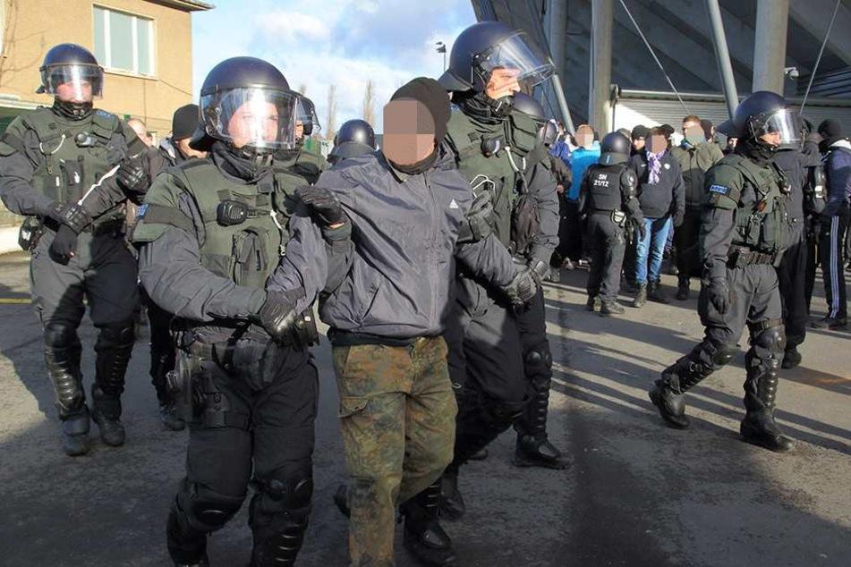 """Polizisten nehmen einen """"Randalierer"""" fest."""