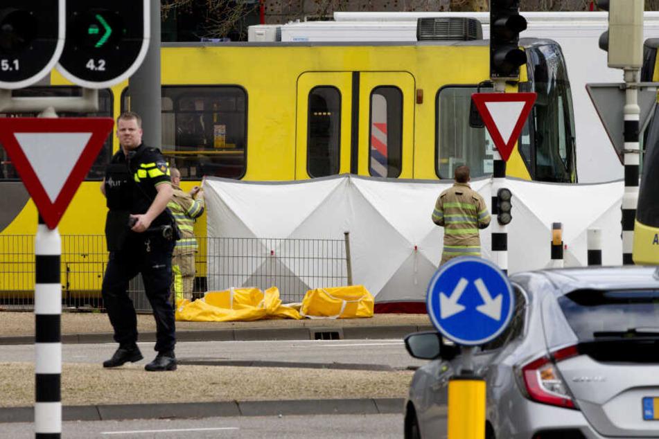Ein Polizist steht an einem Sichtschutz vor einem Straßenbahnwagen.