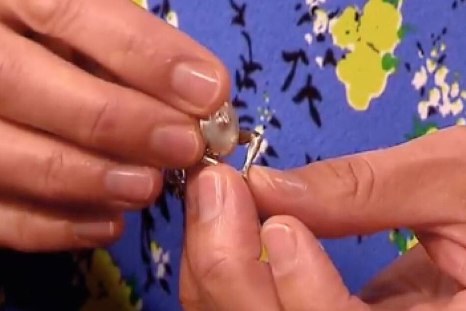 An der Kette der Taschenuhr befindet sich ein Haken in Form einer Frau, die ihre Beine spreizt.