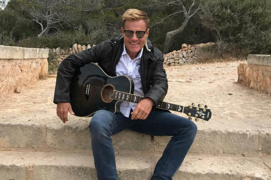 Dieter Bohlen sitzt mit einer Gitarre auf einer Treppe.