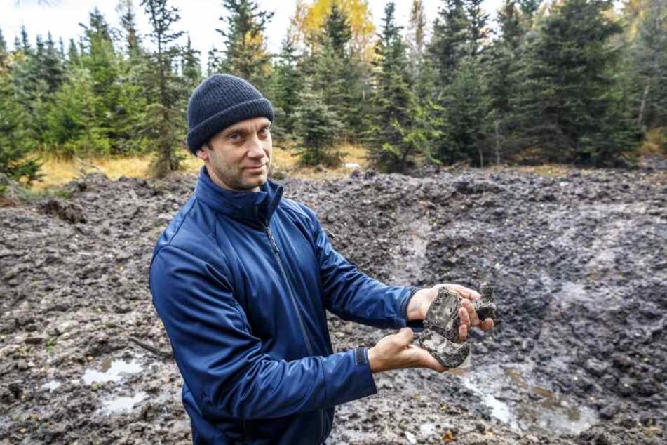 Sprengmeister Thomas Zowalla (41) zeigt gesplitterte Granaten vor dem  Sprengloch.