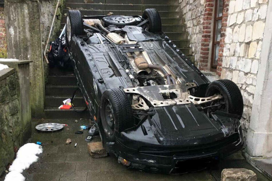 Nachdem es die Treppe herunter gestürzt war, blieb das Auto auf dem Dach liegen.
