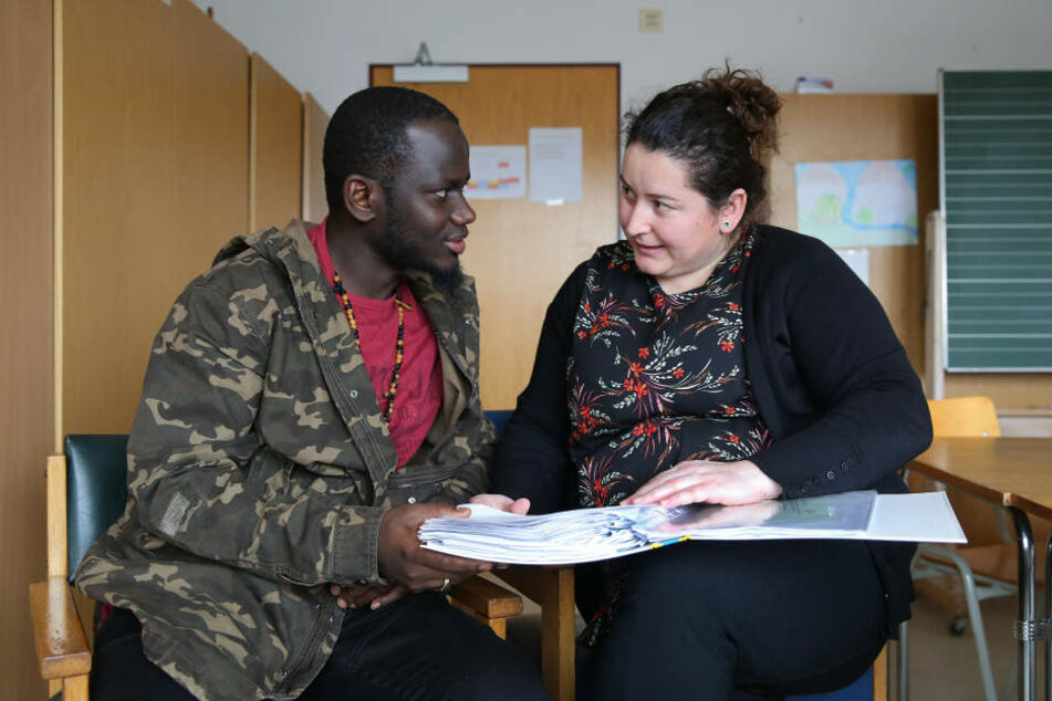 Der Flüchtling Pa Saido Ngum (l.) aus Gambia unterhält sich in einer Flüchtlingsunterkunft mit der Sozialarbeiterin Najla Dervina (r.).
