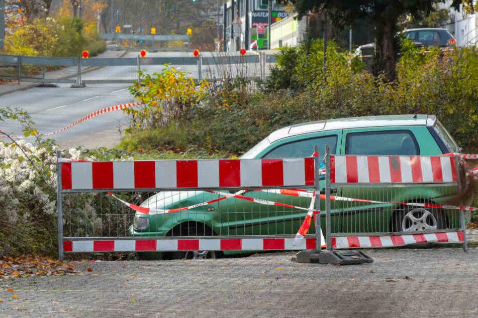 Boden sackt plötzlich ab: Auto steckt in Erdloch fest