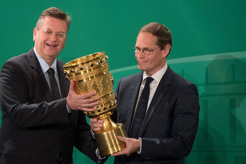 DFB-Präsident Reinhard Grindel (l.) übergibt während der traditionellen Übergabe des DFB-Pokals in Berlin die Trophäe an den Regierenden Bürgermeister der Hauptstadt, Michael Müller (SPD).