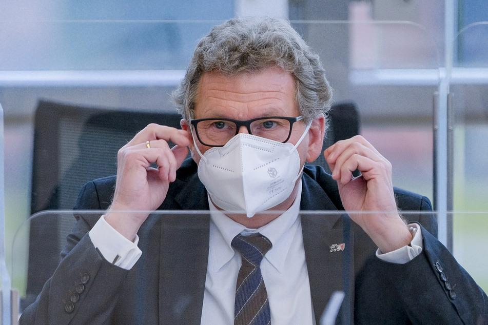 Bernd Buchholz (FDP), Minister des Landes Schleswig-Holstein, setzt sich im Plenarsaal des Landtags eine FFP2-Maske auf.