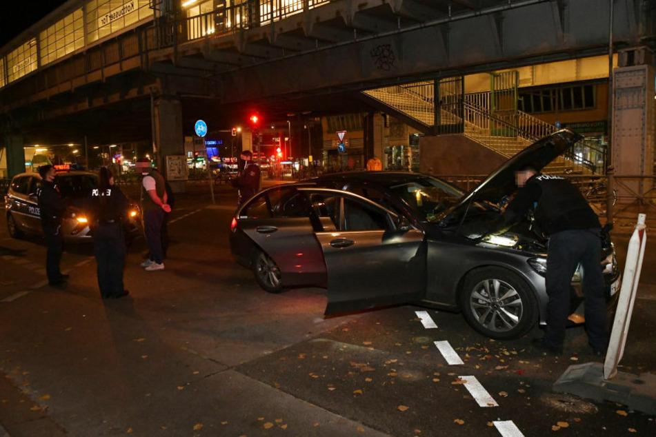 Ein Polizist durchsucht den Motorraum des Mercedes nach verdächtigen Gegenständen.