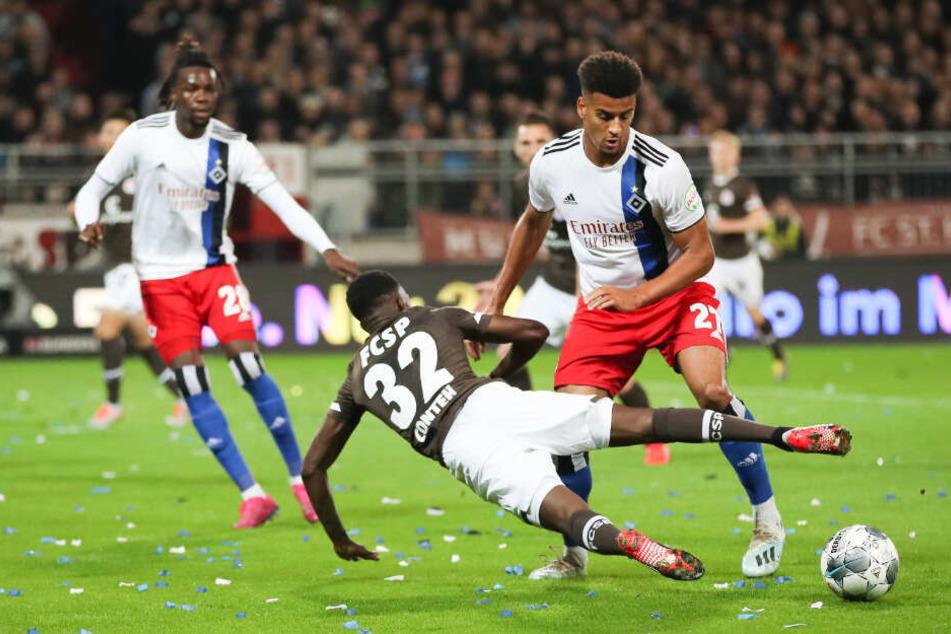 St. Paulis Christian Conteh fliegt in seinem Zweikampf mit HSV-Spieler Josha Vagnoman zu Boden.