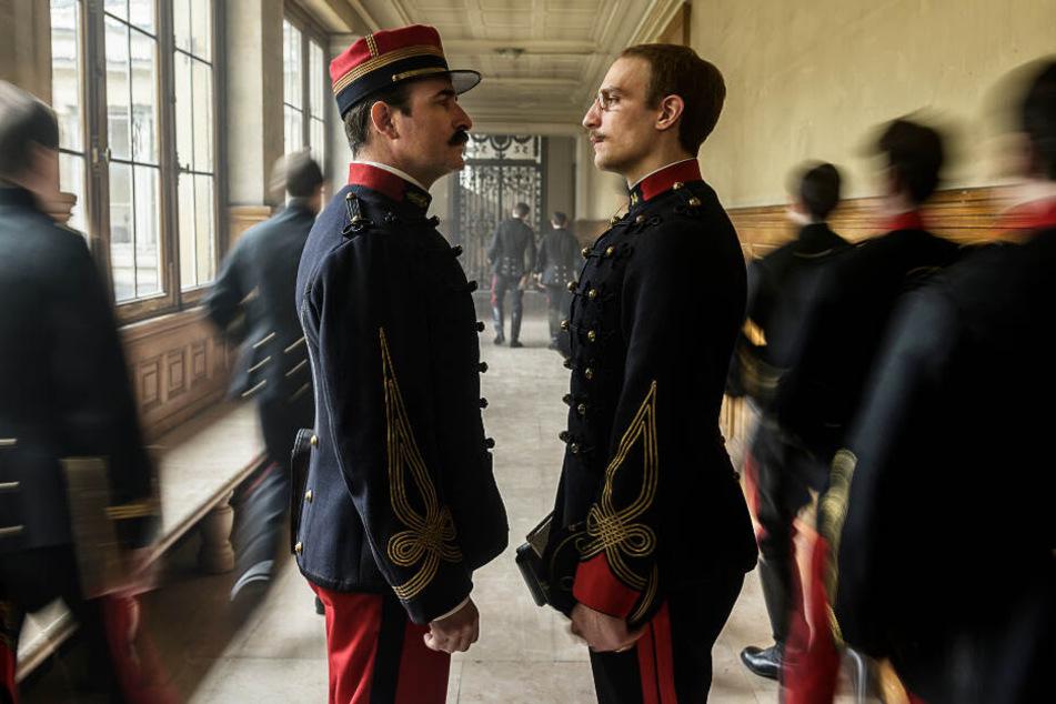 Colonel Georges Picquart (l., Jean Dujardin) und Alfred Dreyfus (r., Louis Garrel) spielen bei der Intrige die Hauptrollen.