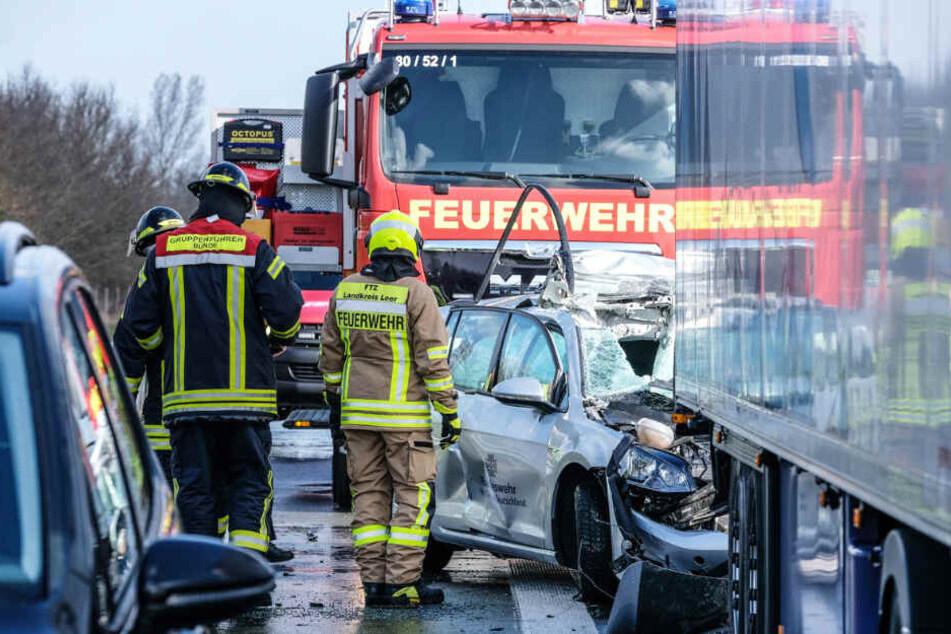 Feuerwehrleute sind an der Unfallstelle auf der A31 im Einsatz. Ein Auto der Bundeswehr geriet unter einen Lastwagen.