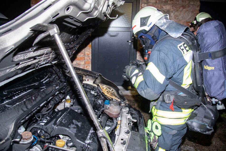 Ein Feuerwehrmann aus Bischofswerda dokumentiert in Schutzkleidung den entstandenen Schaden.