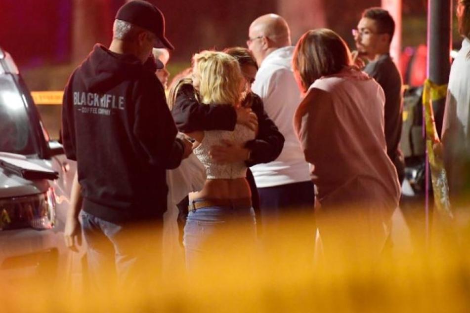 Die Menschen trösten sich gegenseitig in der Nähe einer Bar, in der ein Mann auf Gäste geschossen hat.