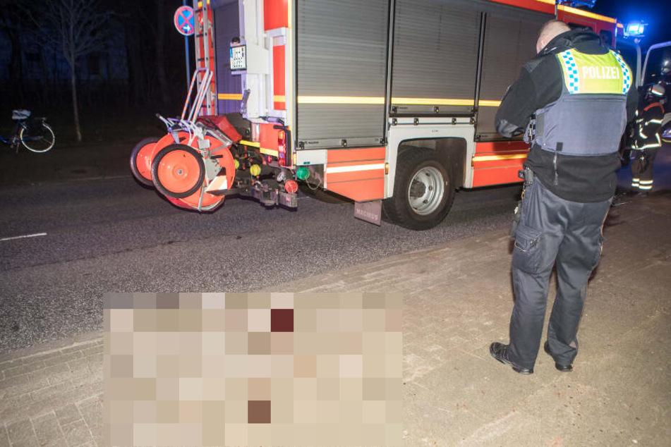 Ein Polizist steht neben einer großen Blutlache auf dem Gehweg.