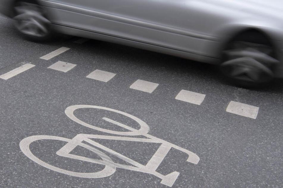 Ein Auto fährt an einer Kreuzung an einem Radweg vorbei.
