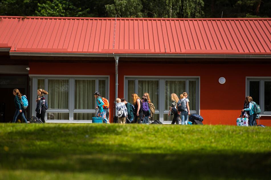 Eine Gruppe Schüler geht mit ihrem Gepäck an einer Unterkunft vorbei.