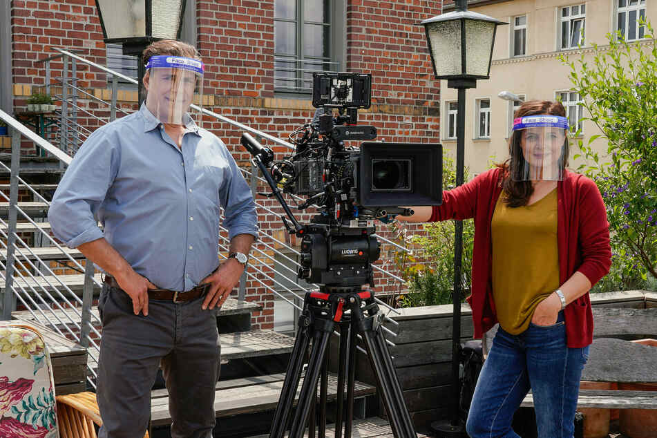 Zum Schutz gegen das Coronavirus tragen die Schauspieler Sven Martinek (Rolle Dr. Christoph Lenz) und Elisabeth Lanz (Rolle Tierärztin Dr. Mertens) Plastikvisiere während der Dreharbeiten.