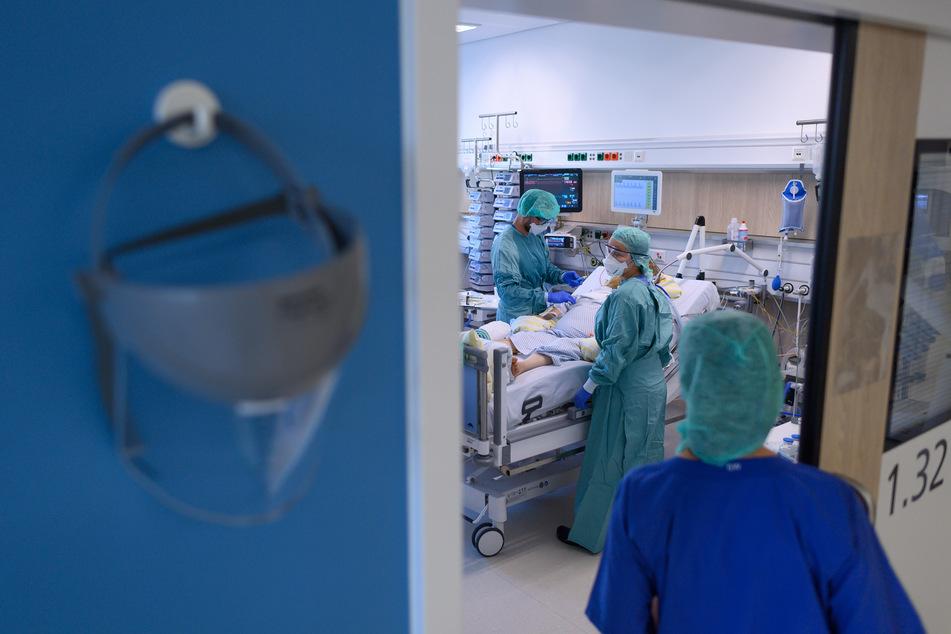 Intensivpfleger sind in der Corona-Intensivstation des Universitätsklinikums Dresden mit der Versorgung von Patienten beschäftigt.