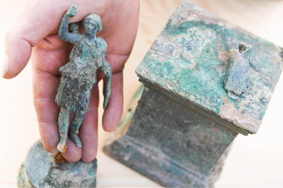 Ein Grabungstechniker präsentiert eine kleine Statue der Göttin Diana sowie den Sockel, auf dem einst die Figur des Merkurs stand.