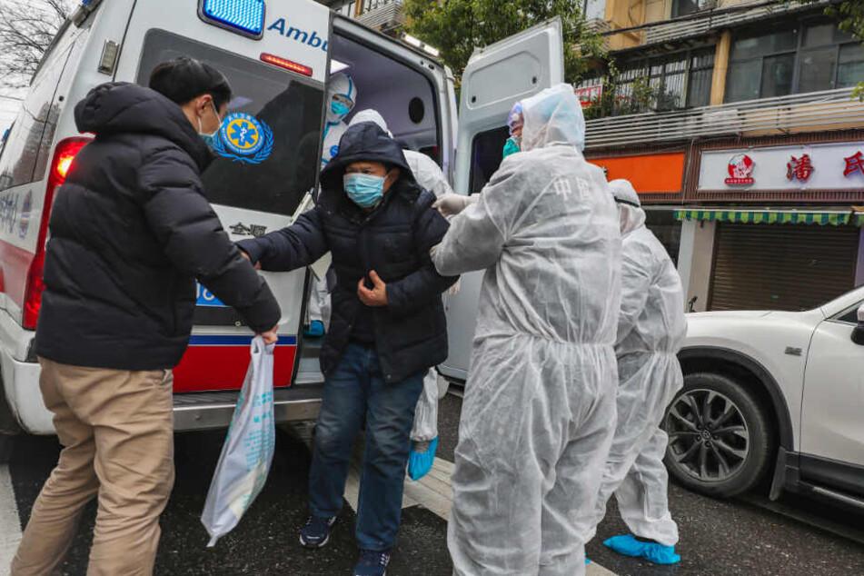 Krankenhausmitarbeiter in Schutzkleidung helfen einem Patienten in Wuhan aus einem Krankenwagen.