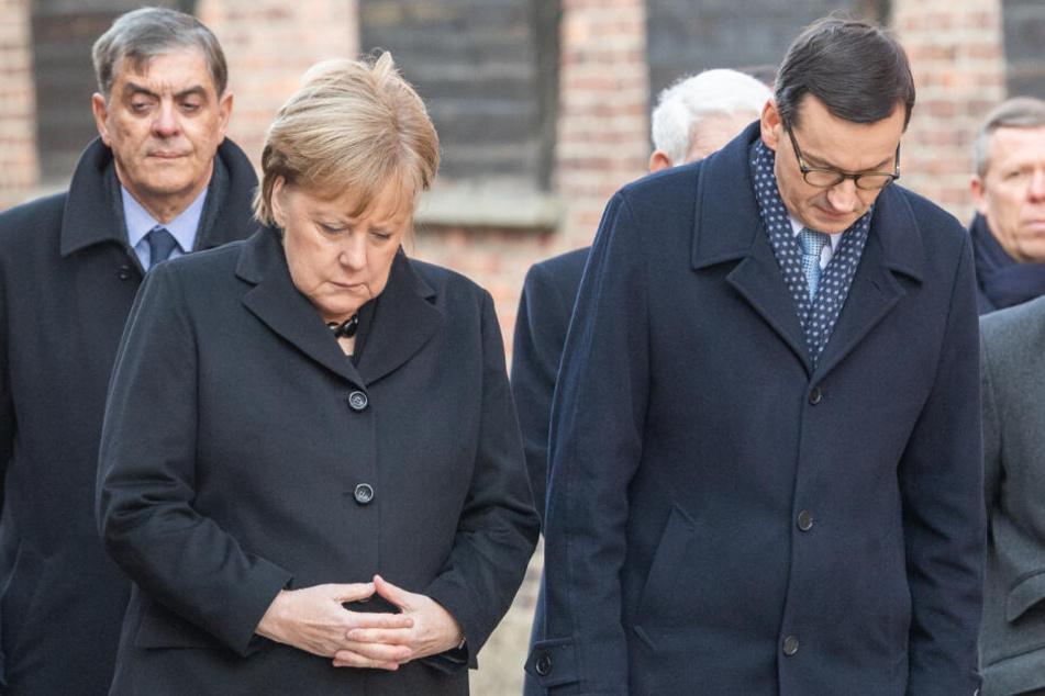 Bundeskanzlerin Angela Merkel (CDU) und Mateusz Morawiecki, Ministerpräsident von Polen, verneigen sich nach einer Kranzniederlegung an der Todesmauer im ehemaligen deutschen Konzentrationslager Auschwitz.