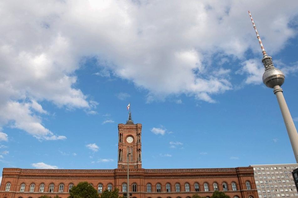 Rotes Rathaus und Fernsehturm werden von einem wolkigen Himmel überspannt.
