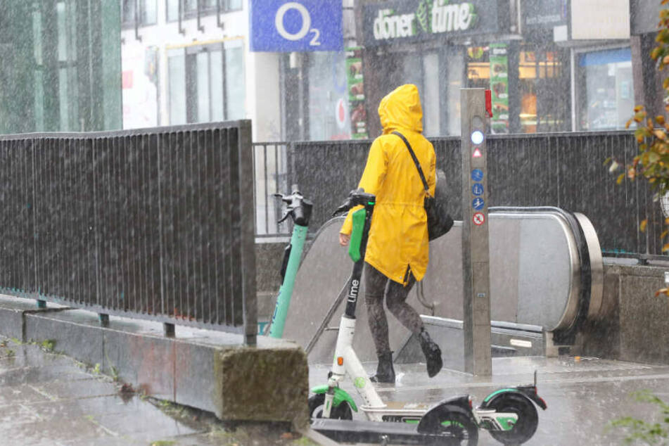 Eine Frau geht im Friesennerz zu einer U-Bahn-Station in Hamburg.