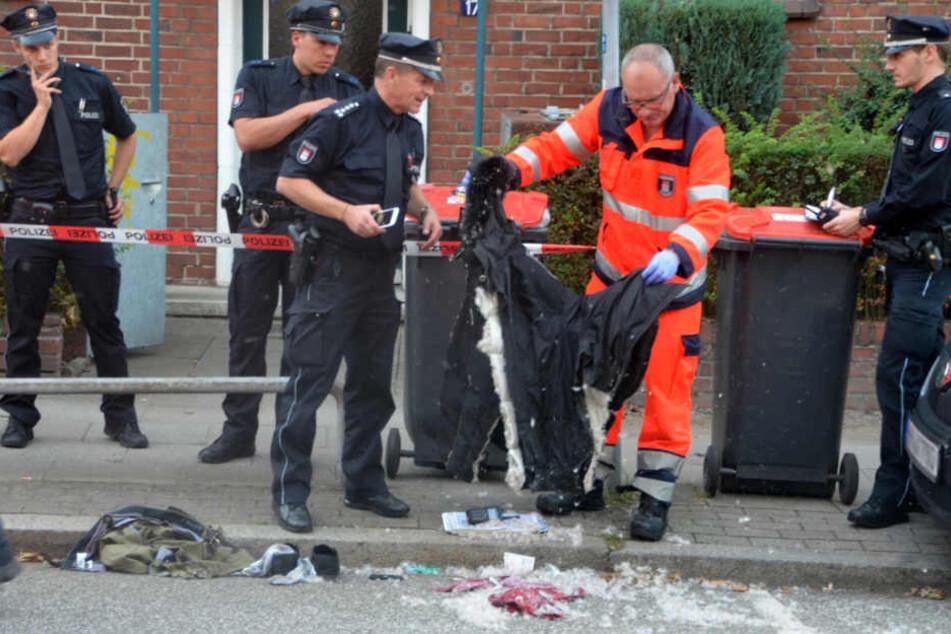 Polizisten sichern in der Nähe des Einkaufszentrums Quarree im Hamburger Stadtteil Wandsbek Beweise.