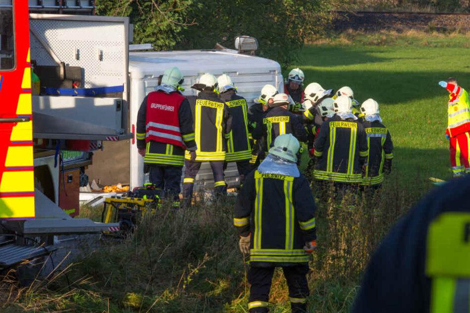 Rettungskräfte versuchen die beiden schwer verletzten Personen aus dem Transporter zu befreien.