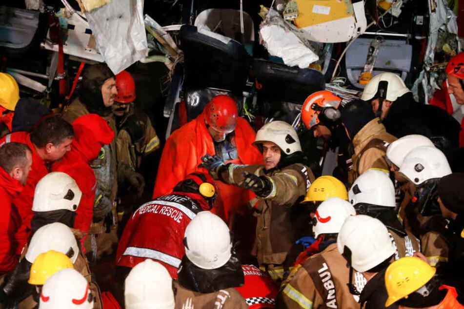 Rettungskräfte evakuieren eine verletzte Person (M) aus dem Wrack des Flugzeugs.