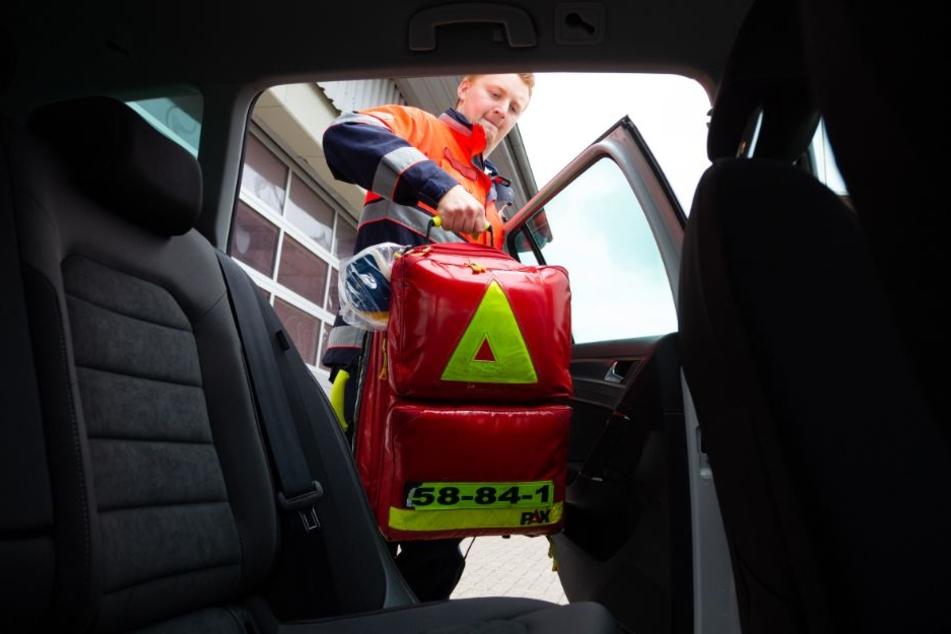 Gemeindenotfallsanitäter Alexander packt seinen Notfallrucksack auf die Rücksitzbank seines Einsatzfahrzeugs.