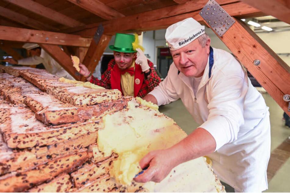 Butter bei die Platten! Bäckermeister Thomas Schmidt (57) schmiert, was das Zeug hält, damit der Riesenstollen eine ordentliche Form bekommt. Tatkräftig unterstützt vom Schabernack eines Clowns vom Dresdner Weihnachts-Circus.