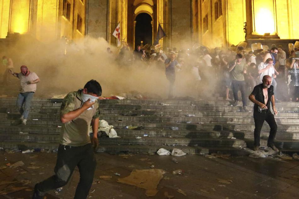 Die Demonstranten halten sich die Augen zu. Die Sicherheitskräfte setzten Tränengas und Wasserwerfer gegen sie ein.
