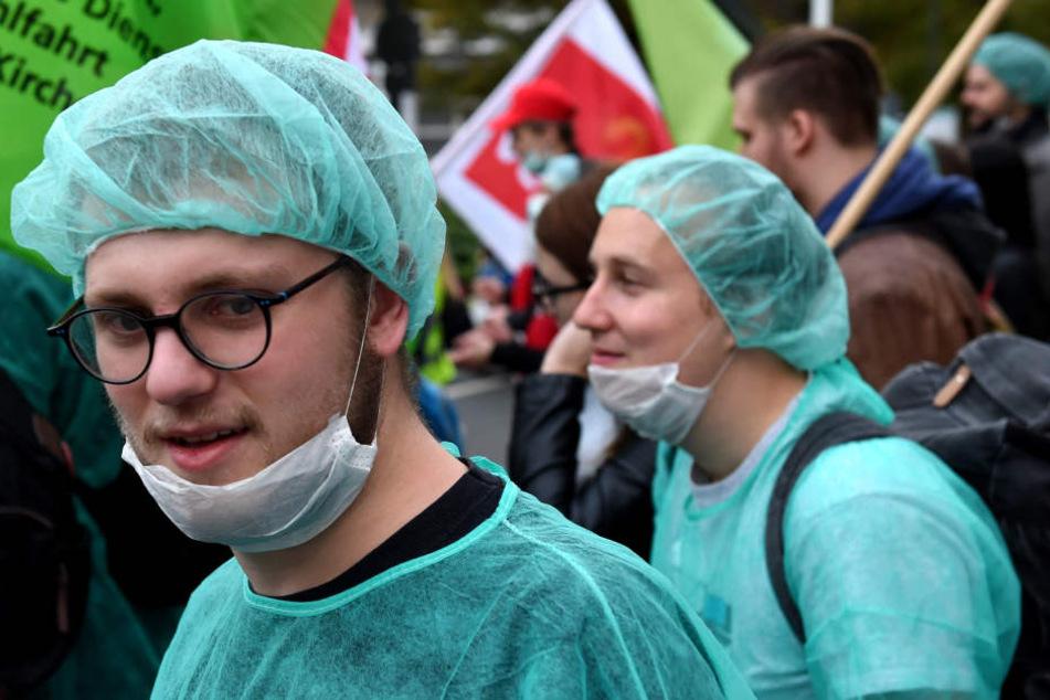 Mitarbeiter der Uniklinik demonstrieren in Düsseldorf in Klinikkleidung. (Archivbild)