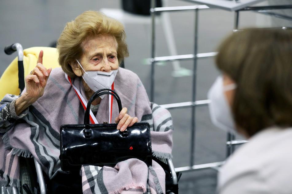 Elisabeth Steubesand (l, 105) spricht im Impfzentrum vor ihrer Impfung mit Henriette Reker (64, parteilos), Oberbürgermeisterin von Köln.