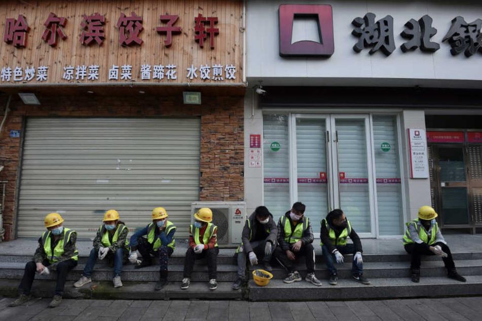 Arbeiter - allesamt mit Mundschutz - machen vor einer geschlossenen Bank und einem Restaurant eine Pause.