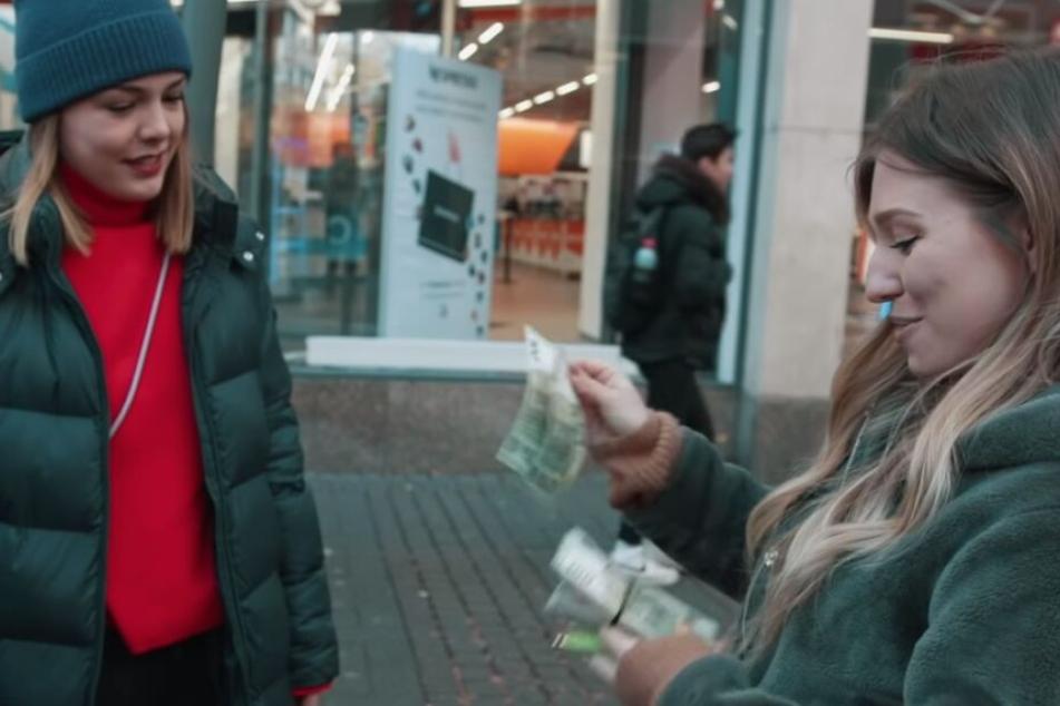 Bibi (rechts) mit einem Bündel voller Geldscheine.