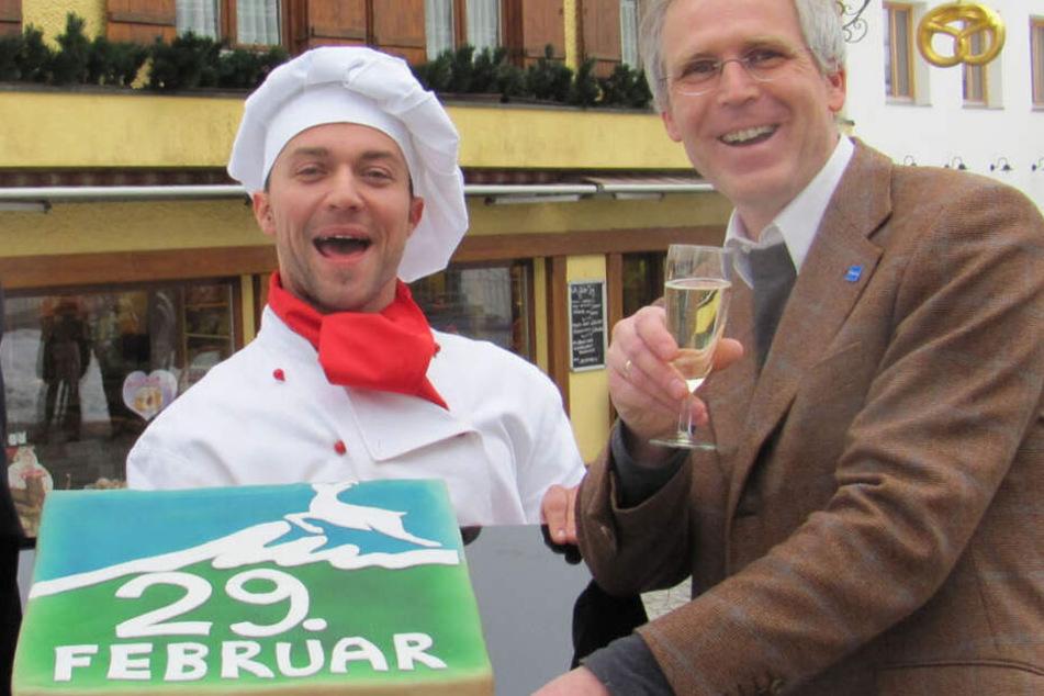 Konditor Florian Kaufmann und Kurdirektor Max Hillmeier präsentieren in Bad Hindelang eine Torte für die Geburtstagskinder. (Archivbild)