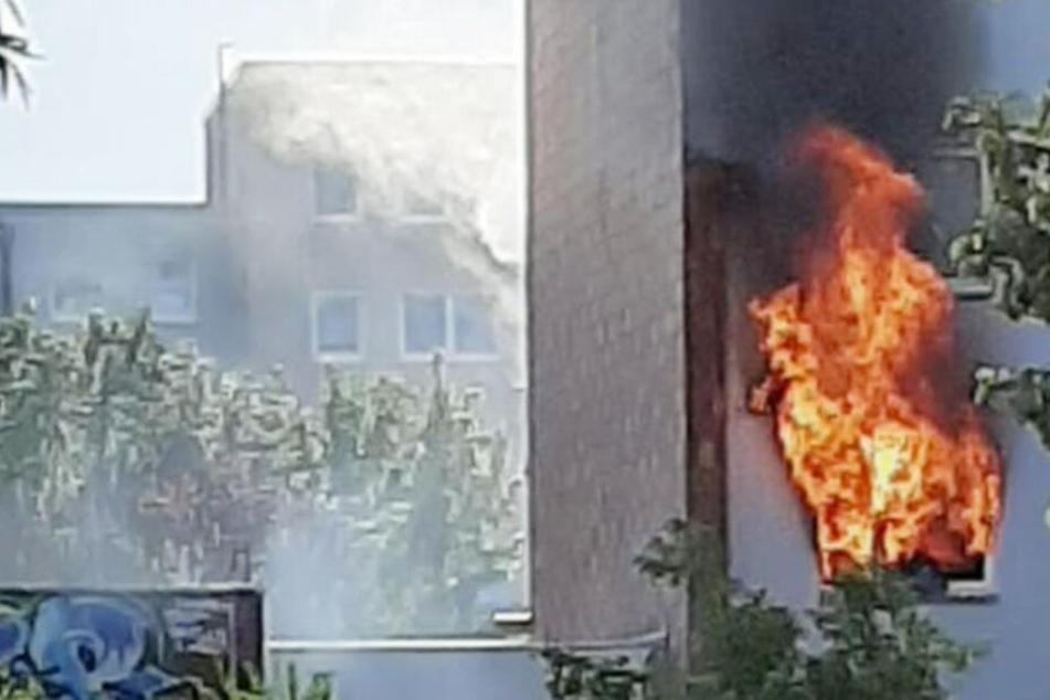 Flammen schlagen aus Wohnung in Mehrfamilienhaus