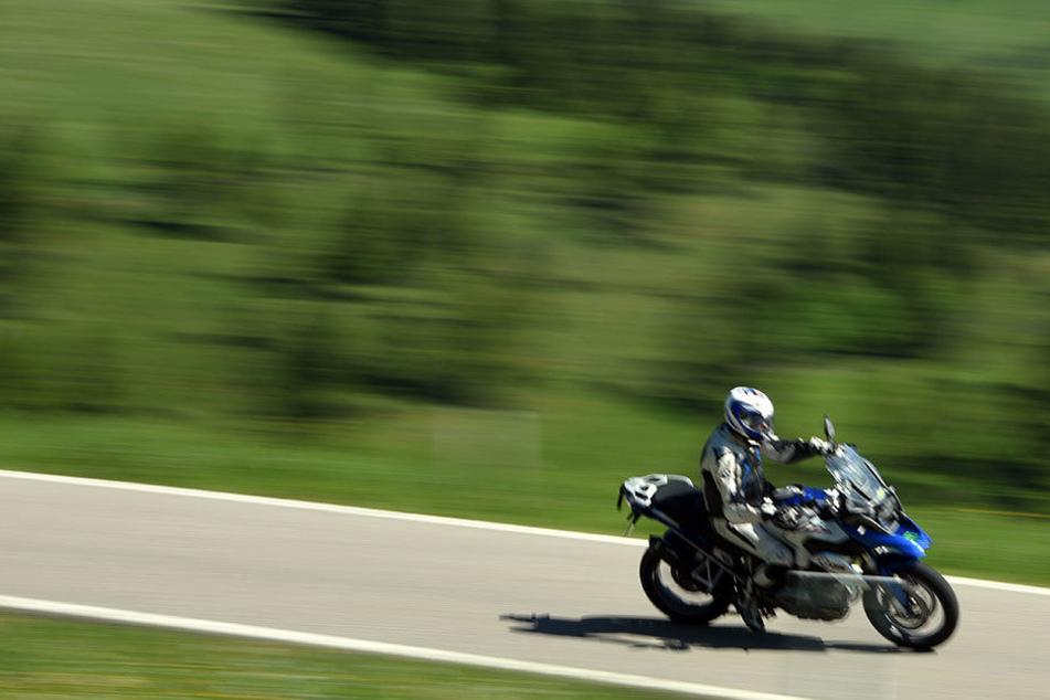Ein Motorradfahrer fährt mit seiner Maschine auf einer Landstraße (Symbolbild)