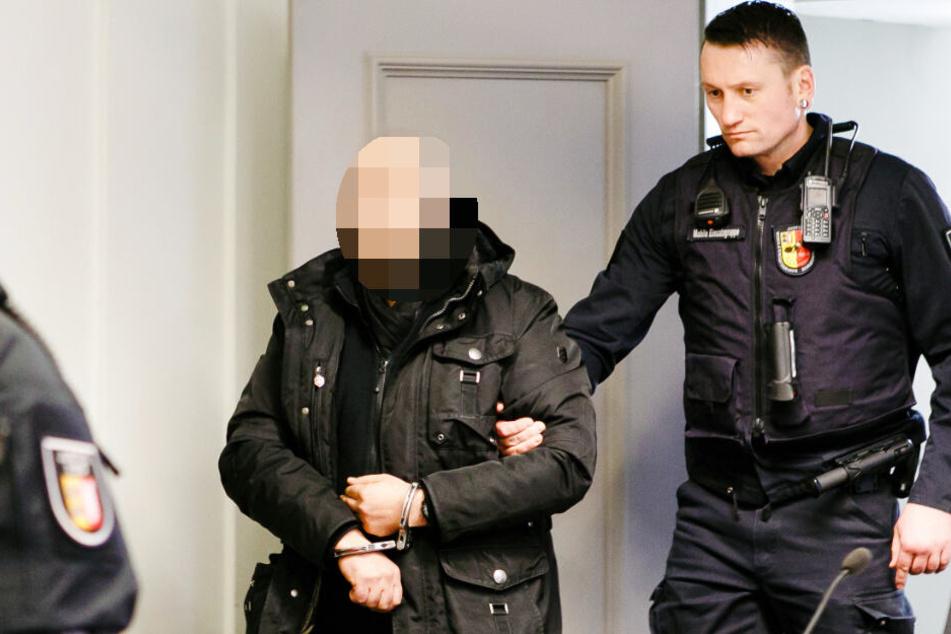 Der Angeklagte wird von einem Justizbeamten in den Gerichtssal des Landgerichts Kiel geführt.
