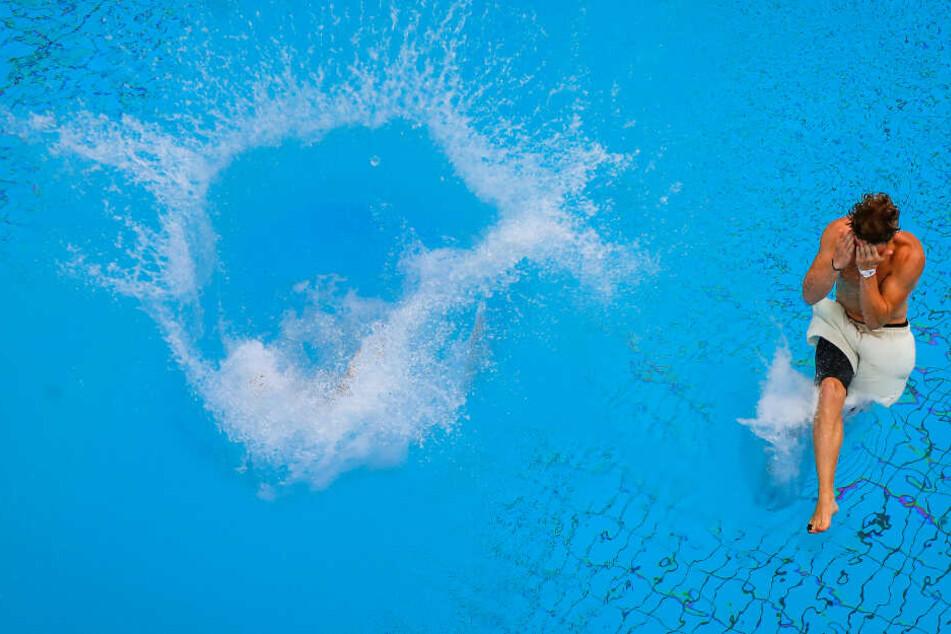 """Zwei Teilnehmer der """"Arschbomben-Weltmeisterschaft"""" (""""Splashdiving"""") tauchen beim Finale in das Wasser vom Sprungbecken ein."""